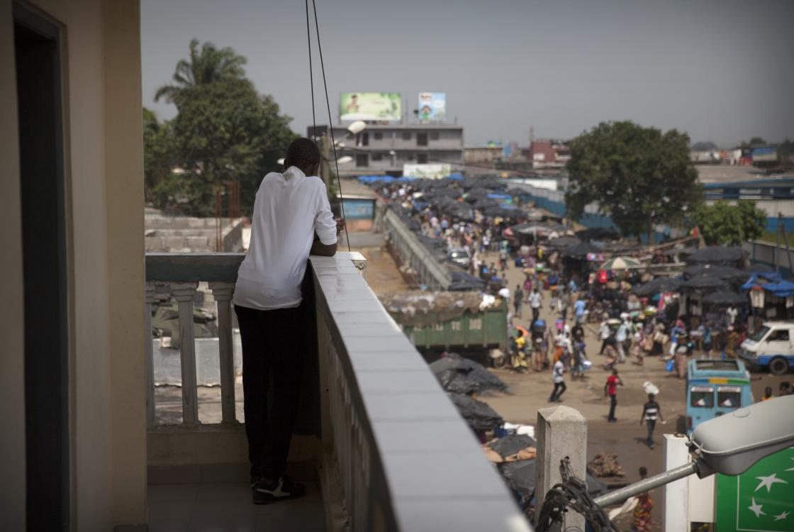 From the balcony, young man watching the street, Côte d'Ivoire