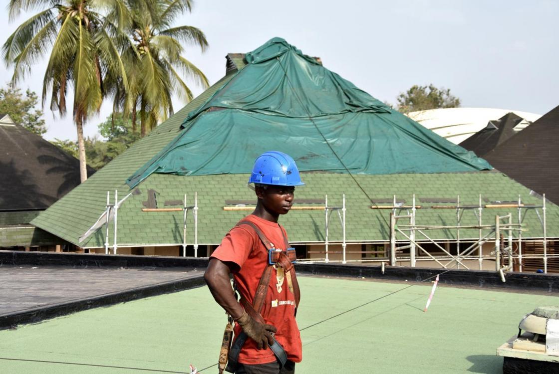 Un ouvrier travaillant à la réhabilitation du toit d'un batiment de l'institut polytechnique de Yamoussoukro