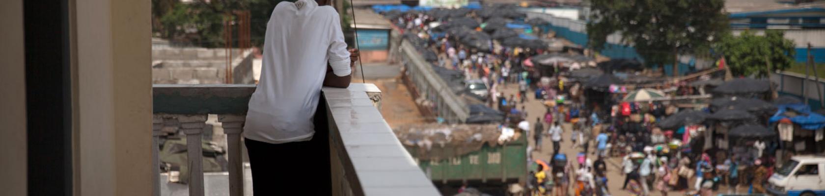 Un jeune homme depuis le balcon regarde la rue animée, Côte d'Ivoire
