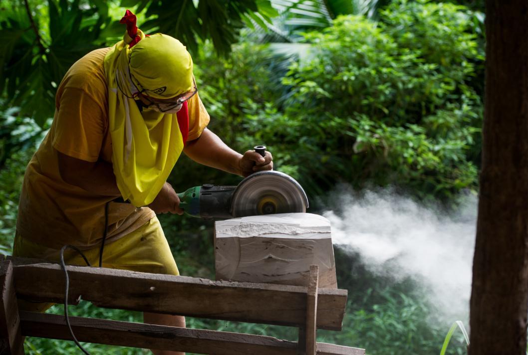 Artisanat, sculpteur façonnant un morceau de roche, Fatu Hiva, Polynésie