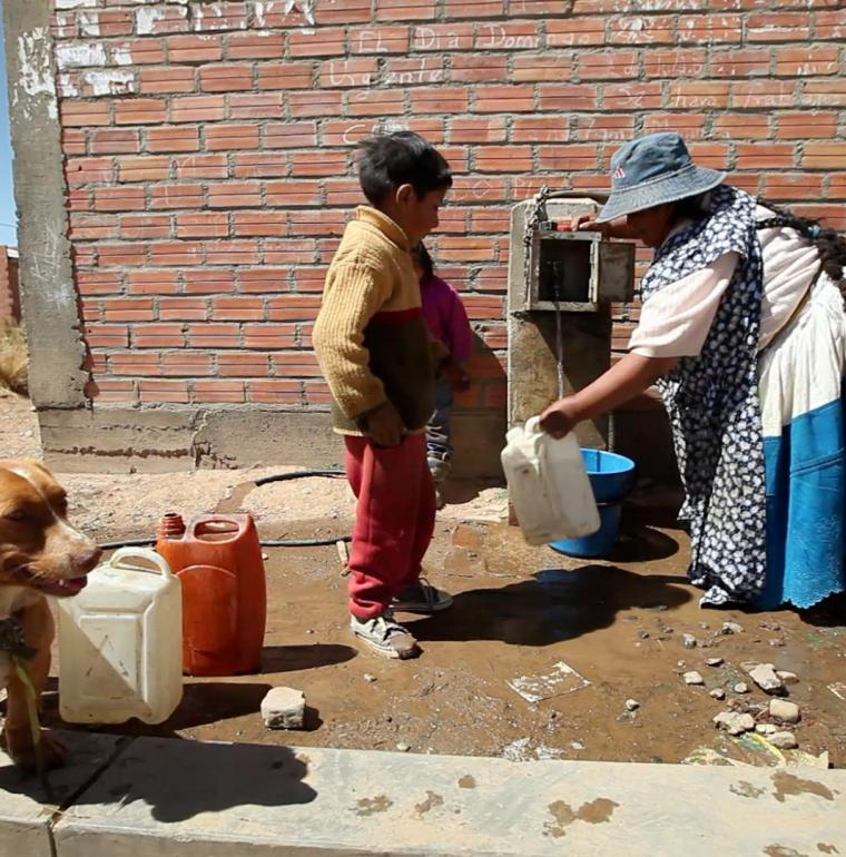 A mother and her child filling up on water at the tap. Alto, Bolivia