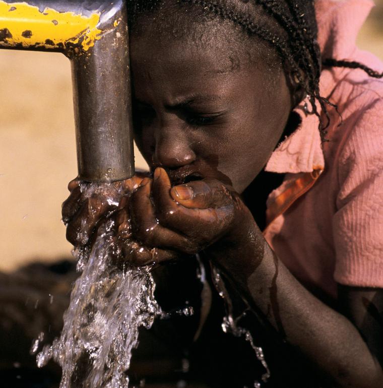 Mali, jeune fille buvant de l'eau fraîche à la pompe