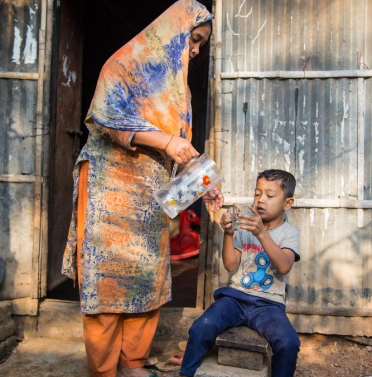 woman serving water to her son, Bangladesh, water supply, clean and healthy water, poor, Agence Française de Développement